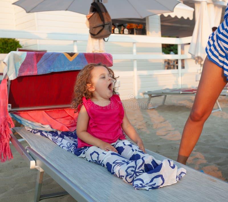 La niña adorable bosteza después de una siesta en la cama de la playa imagenes de archivo