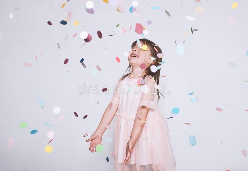 La niña adorable que lleva el vestido rosado en Tulle con la corona de la princesa en la cabeza en el fondo blanco disfruta de so imagen de archivo