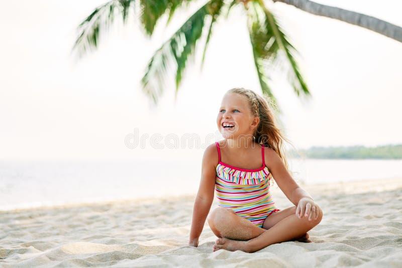 La niña adorable se relaja en la playa arenosa debajo de la palmera con el espacio de la copia fotos de archivo