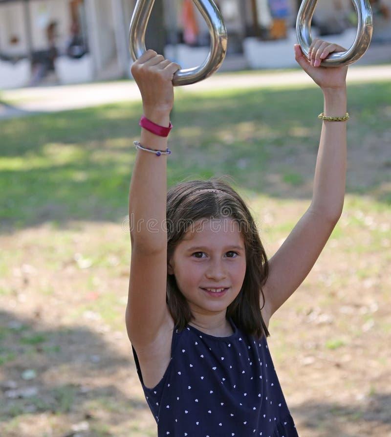 La niña agradable mientras que realiza ejercicio ejercita en el anillo foto de archivo libre de regalías
