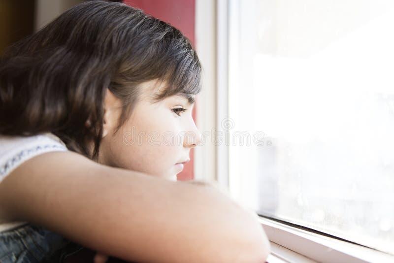 La niña agradable por la ventana siente triste foto de archivo libre de regalías