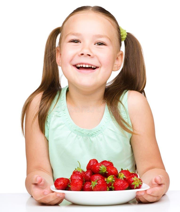 La niña alegre está comiendo las fresas fotografía de archivo
