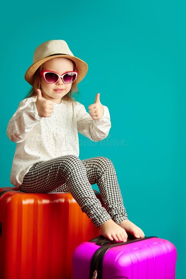 La niña alegre va a disparar, sentándose en las maletas, llevando un sombrero de paja y las gafas de sol, los pulgares de las dem imagenes de archivo