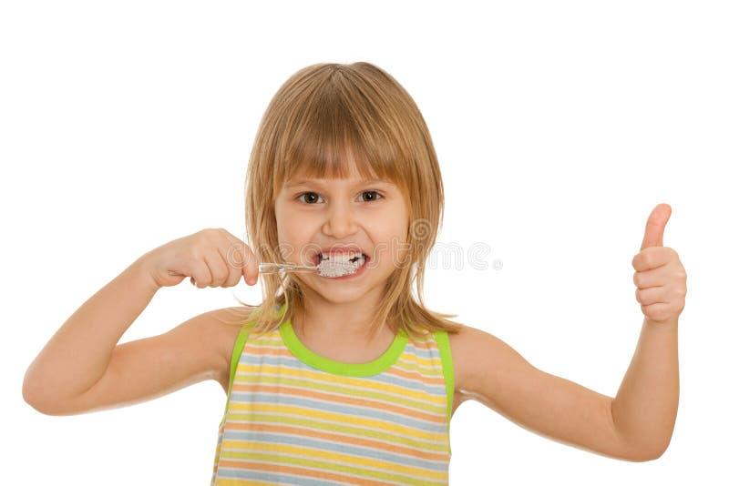 La niña aplica sus dientes con brocha fotografía de archivo libre de regalías