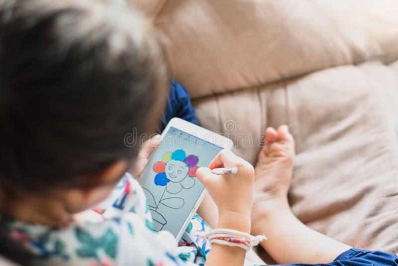 La niña ascendente cercana de los niños está dibujando en el aprendizaje y el desarrollo de los smartphones con tecnología imagen de archivo libre de regalías