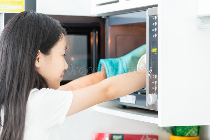 La niña asiática saca de la comida la microonda cuidadosamente, niño lindo con los guantes protectores en sus manos en la cocina  fotos de archivo libres de regalías