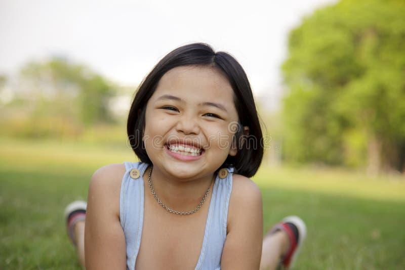La muchacha se relaja y sonriendo feliz en el parque imágenes de archivo libres de regalías