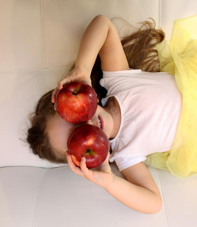 La niña atractiva está sosteniendo una manzana roja dos en su mano imagen de archivo libre de regalías