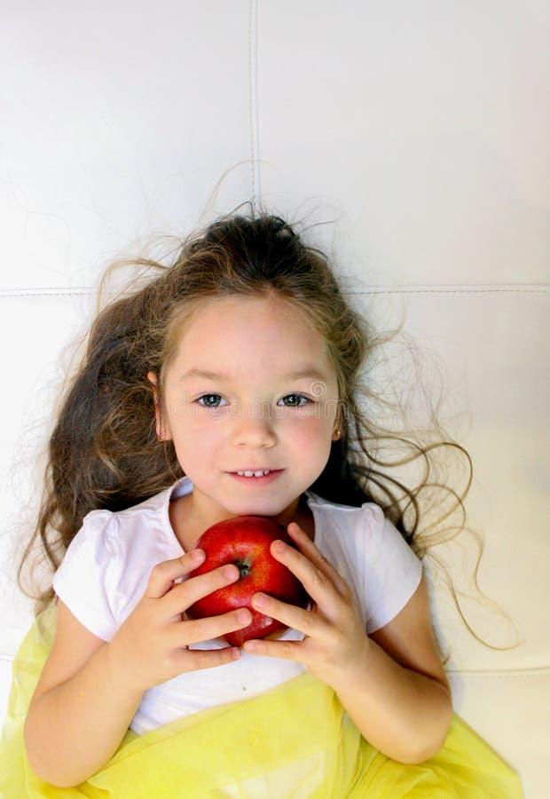 La niña atractiva está sosteniendo una manzana roja en su mano imagenes de archivo