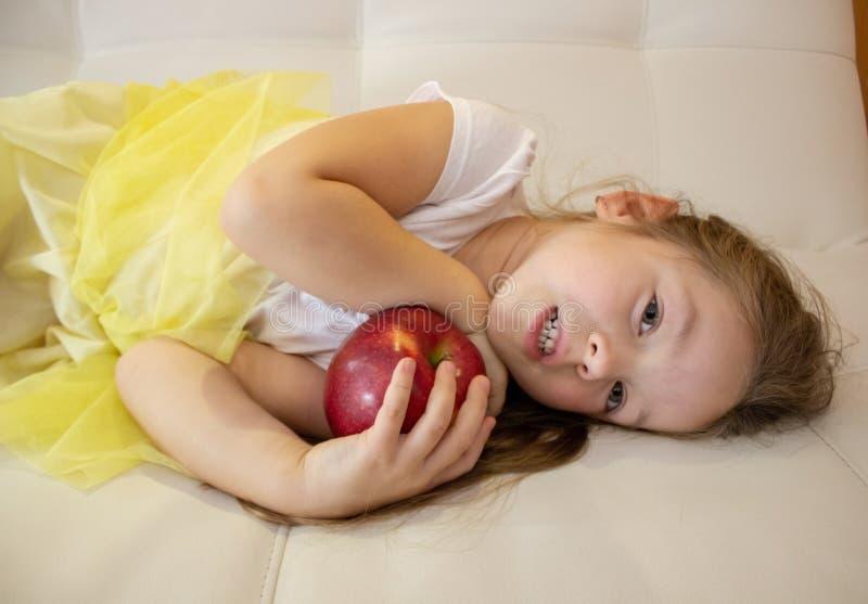 La niña atractiva está sosteniendo una manzana roja en su mano imagen de archivo