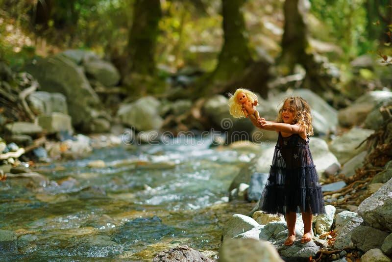 la niña baña una muñeca en un río de la montaña imágenes de archivo libres de regalías