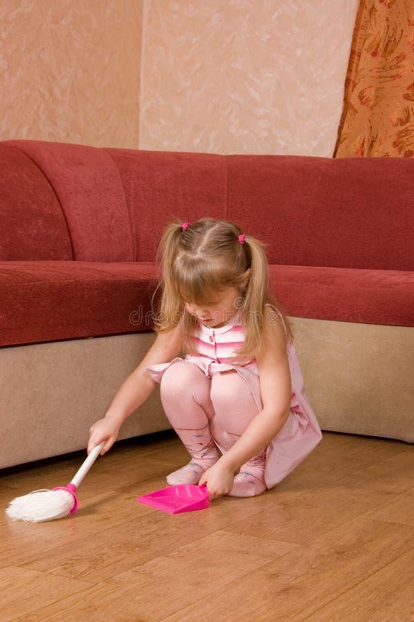 La niña barre un suelo fotografía de archivo libre de regalías