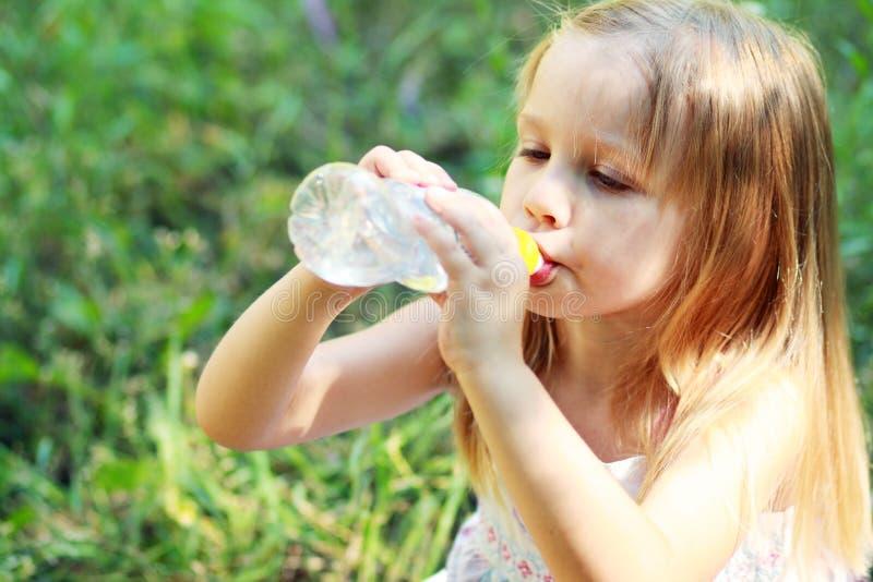 La niña bebe el agua mineral imágenes de archivo libres de regalías