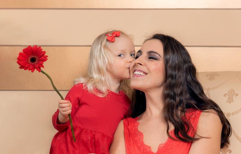 La niña besa a su mamá imagen de archivo