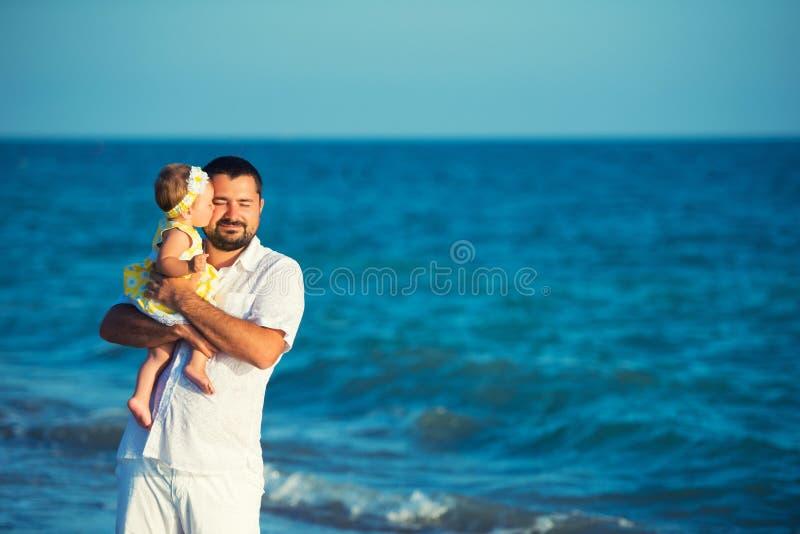 La niña besa a su papá Padre feliz que juega con la pequeña hija linda en la playa fotos de archivo libres de regalías