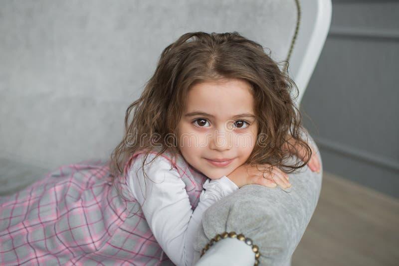 La niña bonita con el pelo marrón se sienta en un sofá gris imagen de archivo