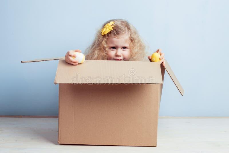 La niña bonita con la flor amarilla en su pelo y teñió los huevos en sus manos se sienta en la caja de cartón en el fondo fotos de archivo