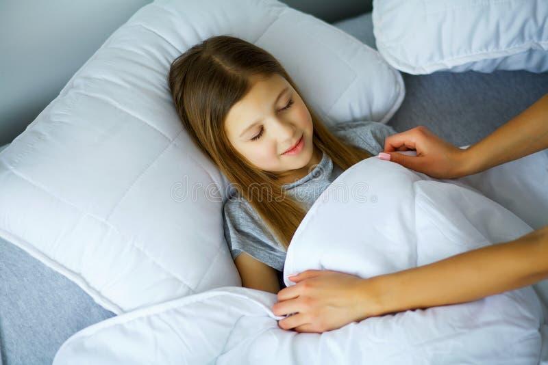 La niña bonita está durmiendo en cama en casa, mamá está cubriendo h imagen de archivo