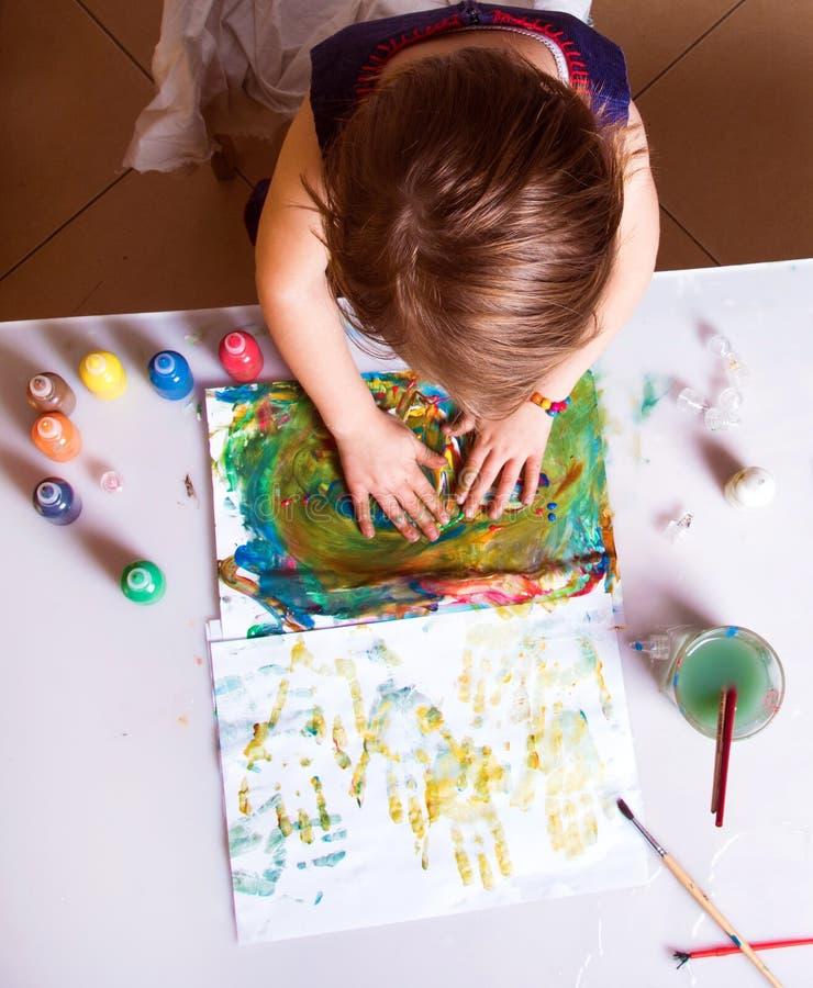 La niña bonita hermosa dibuja una imagen abstracta del PA imágenes de archivo libres de regalías