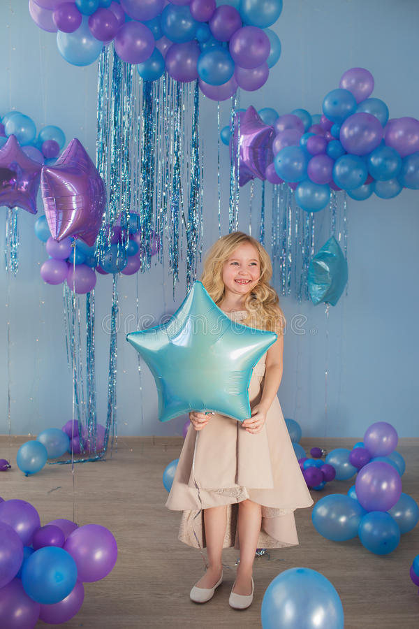 La niña bonita se coloca con los globos (la estrella) foto de archivo