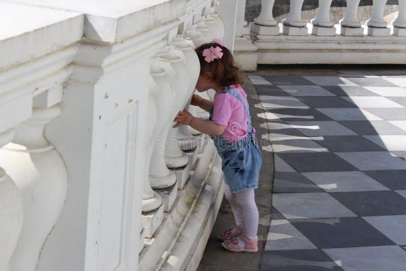 La niña camina en el parque y las miradas a través de la cerca del biton imagen de archivo