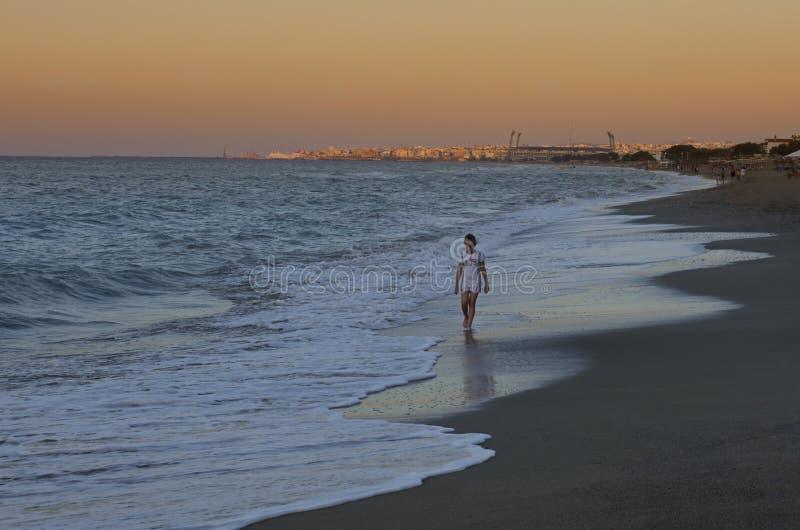 La niña camina a lo largo de la costa contra la puesta del sol foto de archivo