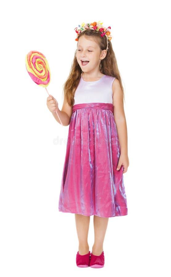 La niña, caramelo en el palillo, embroma el dulce fotos de archivo