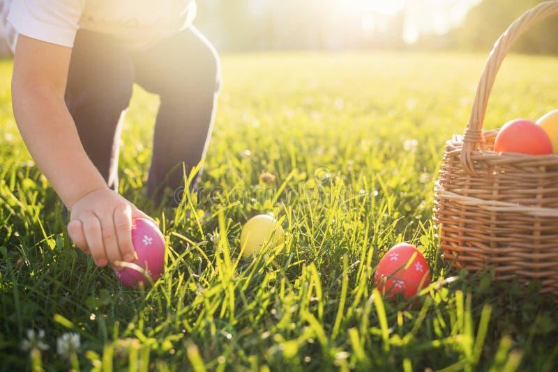 La niña caza el huevo de Pascua Niño que pone los huevos coloridos en una cesta imágenes de archivo libres de regalías