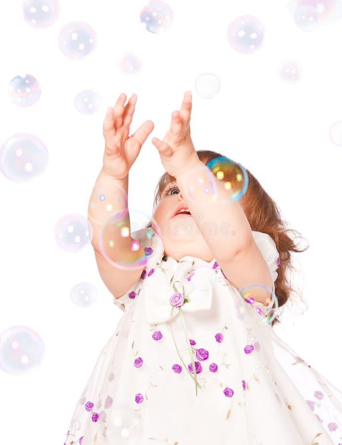 La niña coge las burbujas fotografía de archivo