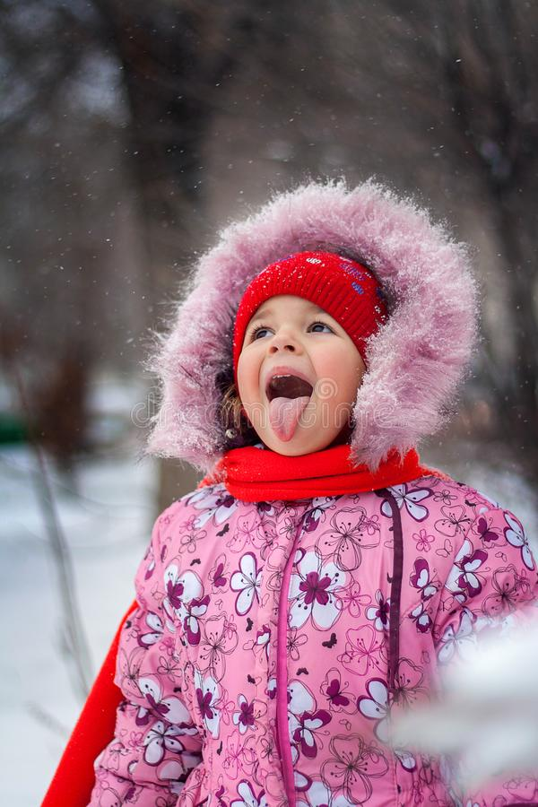 La niña coge una boca del copo de nieve en paseo en el parque imágenes de archivo libres de regalías