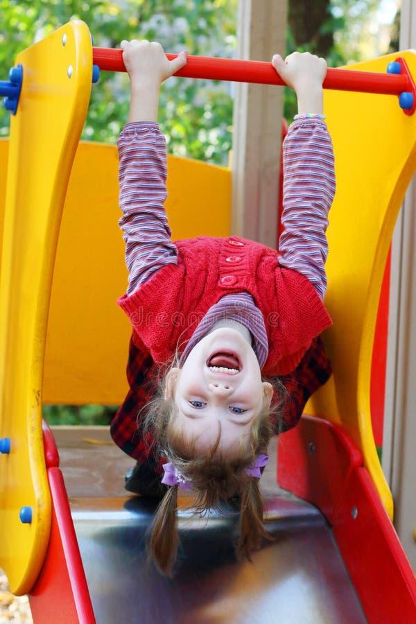 La niña colgó a mano la cabeza abajo en patio fotos de archivo