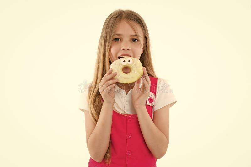 La niña come el buñuelo aislado en blanco Niño con el buñuelo esmaltado del anillo Niño con la comida basura Comida para el bocad fotografía de archivo