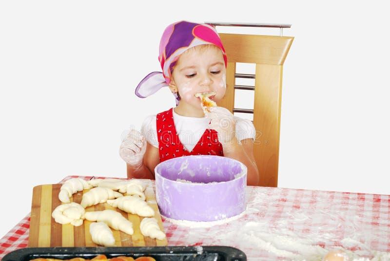 La niña come el croissant imagenes de archivo