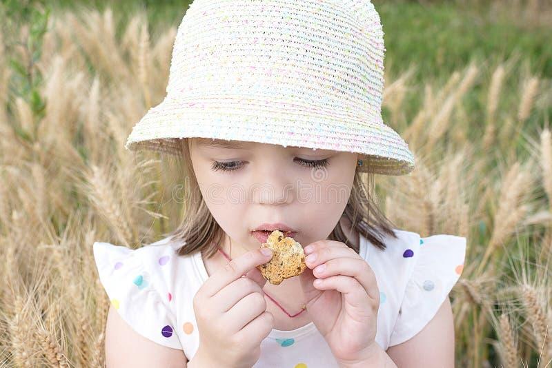 La niña come la galleta en el aire abierto foto de archivo