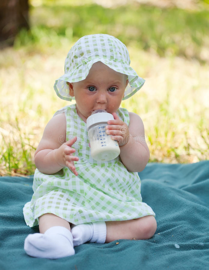 La niña come independientemente una mezcla de la lechería imagen de archivo libre de regalías
