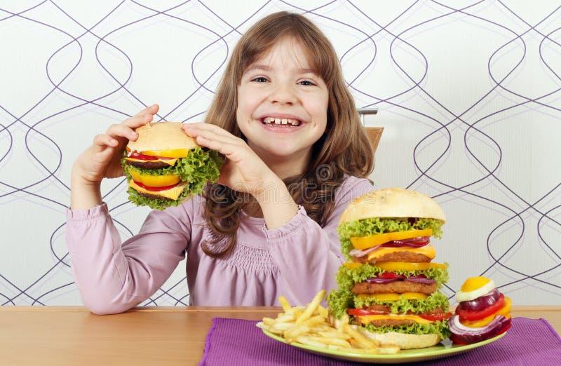 La niña come la hamburguesa fotografía de archivo libre de regalías