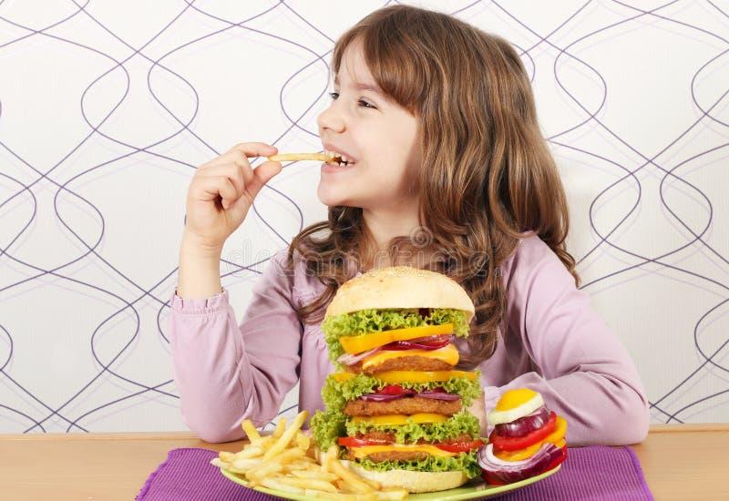 La niña come las patatas fritas y la hamburguesa grande imágenes de archivo libres de regalías