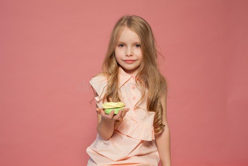 La niña come la torta dulce con la magdalena poner crema fotos de archivo