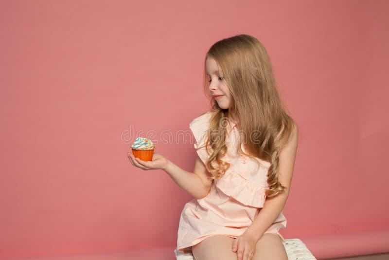 La niña come la torta dulce con la magdalena poner crema foto de archivo
