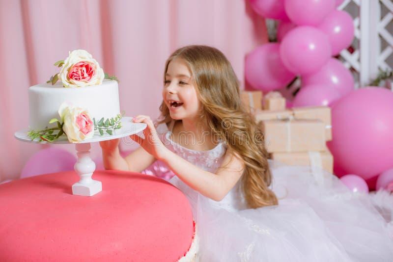 La niña con el pelo largo rubio celebra el partido del feliz cumpleaños con la decoración color de rosa imagen de archivo