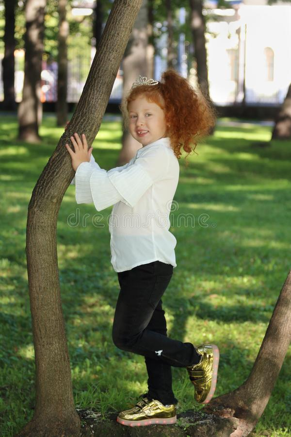 La niña con el pelo rojo en zapatillas de deporte presenta cerca de árbol fotos de archivo