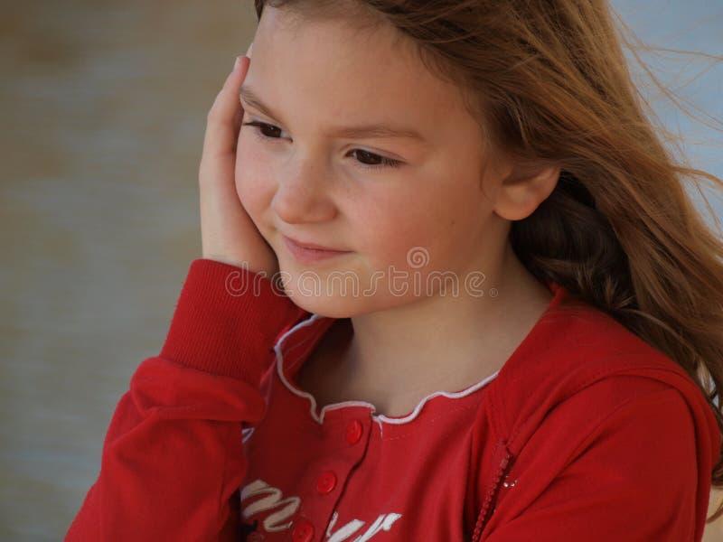 La niña con el pelo rubio que fluía en un suéter rojo puso su mano en su mejilla y sonrisas imagenes de archivo