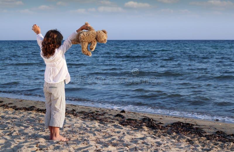La niña con el peluche refiere la playa fotografía de archivo