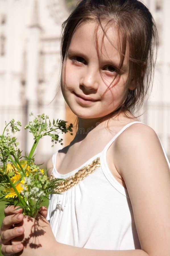 La niña con el ramo del campo florece foto de archivo