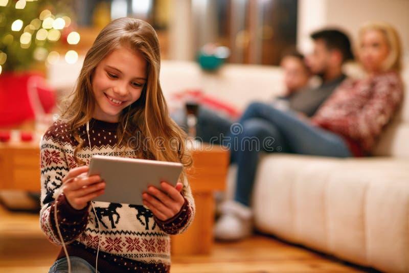 La niña con los auriculares escucha música en la tableta y la sonrisa foto de archivo libre de regalías