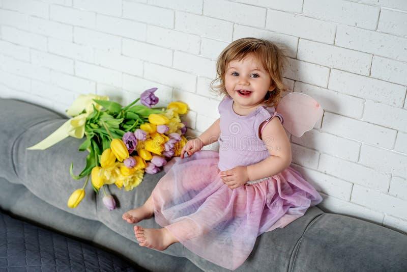 La niña con los tulipanes en ropa de hadas se sienta en una cama Humor del resorte imagenes de archivo