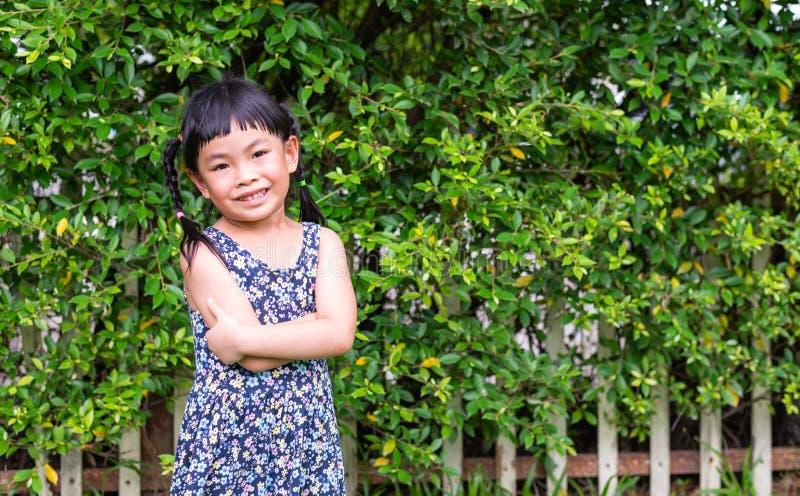 La niña con la sonrisa grande, control arma en pecho foto de archivo