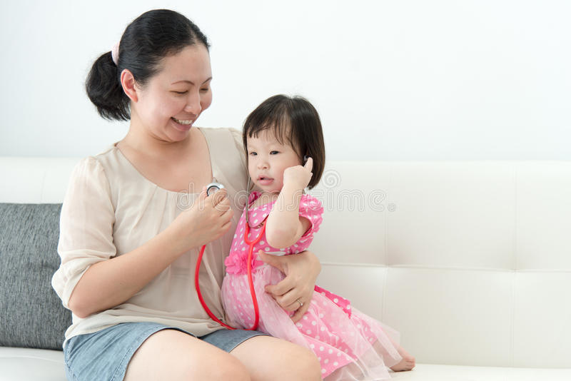 La niña con su madre jugó en doctores imagenes de archivo