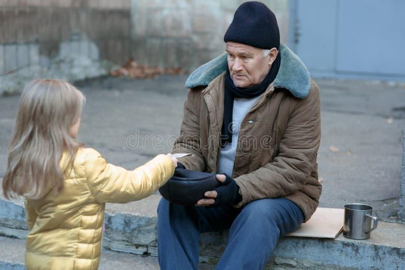 La niña da el dinero al mendigo imágenes de archivo libres de regalías