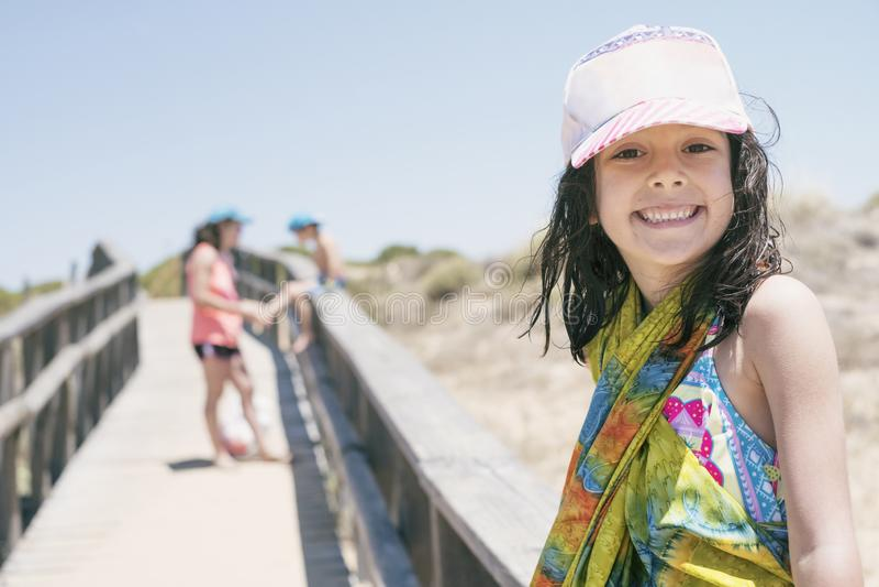 La niña de 6 años mira la cámara después de un día de vacaciones de la playa, envuelto en pareo mientras que en el fondo su madre fotos de archivo libres de regalías